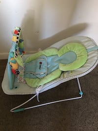 baby's white, blue, and green bouncer with mobile