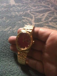round gold-colored and red analog watch with link