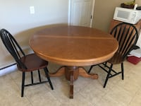 Round brown wooden table with four chairs dining set Frederick