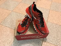 pair of red-and-black Saucony running shoes with box