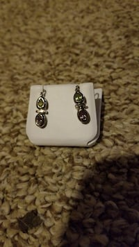 women's silver-colored earrings with clear gemstones