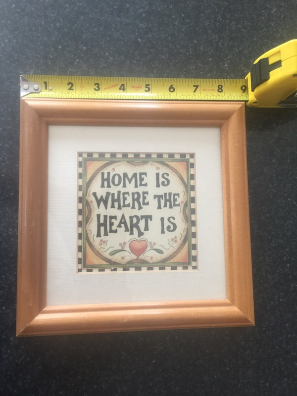 Home is where the heart is wooden quotation board with brown wooden frame