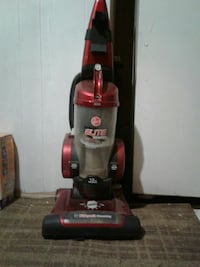 red and black Bissell upright vacuum cleaner