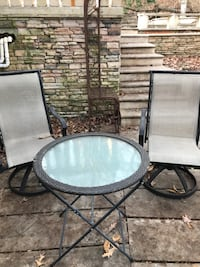round black metal framed glass top patio table