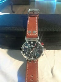 round silver chronograph watch with brown leather