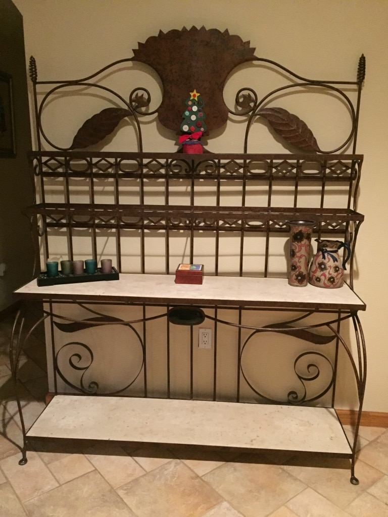 Photo Brown iron bakers rack. Middle and bottom shelves are faux stone finish, top and second are glass. Very heavy and in great condition.
