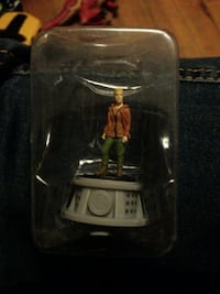 person in brown jacket and green pants plastic figure