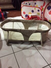 baby's brown and white travel cot