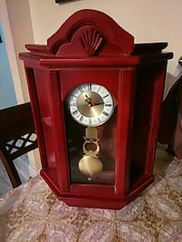 brown wooden pendulum clock with cabinet
