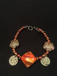 Hand made orange and gold tone bracelet  Vanceboro, 28586