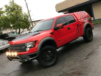 red Ford crew cab truck with campershell