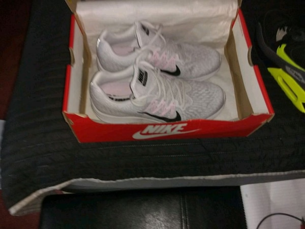 pair of white Nike running shoes in box
