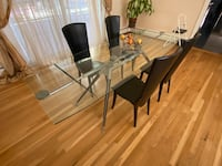 Glass dining room table with 4 black leather chairs