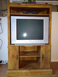 gray CRT TV with brown wooden TV hutch null