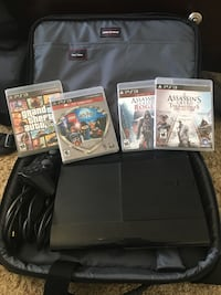 black Sony PS3 super slim console with game cases