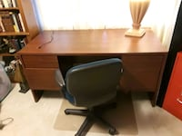 brown wooden desk and black rolling armchair