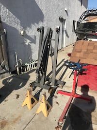 Gray metal engine hoist and pair of yellow jack stands with engine stand