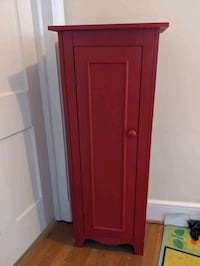 Tall red wood storage cabinet with door