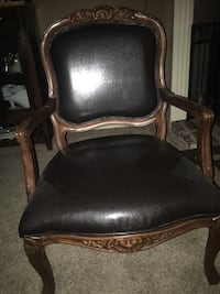 Brown wooden framed black leather padded armchair