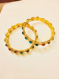 two gemstone-encrusted gold-colored bangles