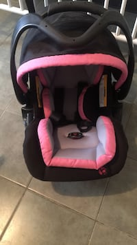 baby's pink and black car seat carrier