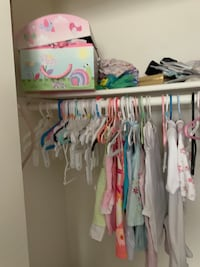 Various baby girl clothes and bears and other little knickknacks