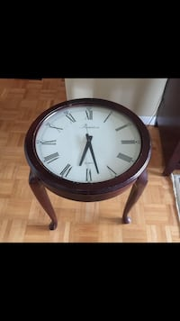 Dark brown Battery operated three legged clock table. Scratched can be painted or re-finished if you so choose. Easy to read :) Mississauga