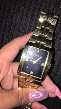 rectangular black and gold Guess analog watch with gold link strap