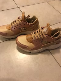 pair of brown-and-white Nike Huarache shoes