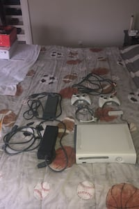 Xbox 360 with two controllers headset 2 power bars and a wifi connect
