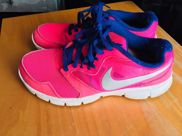 pair of pink-and-blue Nike running shoes