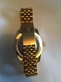 round gold and black Rolex watch with gold link bracelet