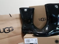 pair of black Ugg patent leather boots on box