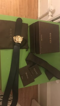 silver Gucci buckled with black leather belt with black box