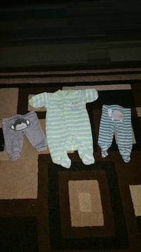 baby's green striped pajama footie and two pairs of pajama pants