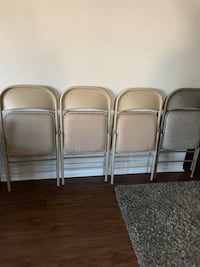 four gray metal folding chairs