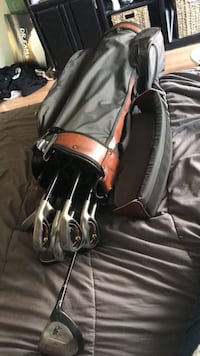 gray golf clubs with black and brown golf bag
