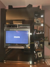 black flat screen TV with brown wooden TV hutch New York, 10469