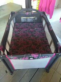 baby's gray and purple floral travel cot