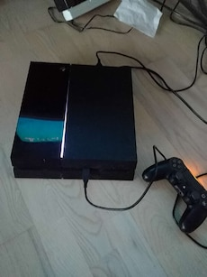 black Sony PlayStation game console with game cont