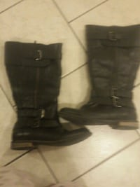 pair of black leather triple-buckled high-top boot