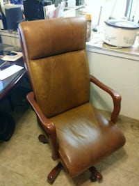 brown wooden framed brown leather padded armchair