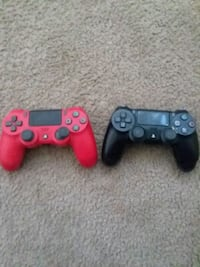 two red and black Sony PS4 controllers