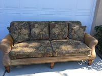 brown and green floral loveseat with pillows