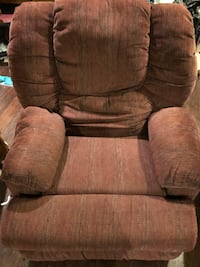 Maroon/burgundy rocking recliner with massage and storage in the arms.