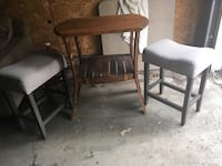 two black wooden frame white padded chairs and brown wooden table set