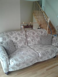 Gray and white floral fabric loveseat