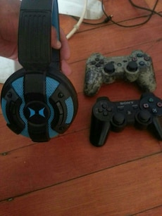 black and blue wireless headphones;two brown and black Sony PS3 controllers