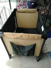 black and beige travel cot