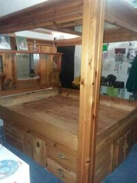 Cal. King wooden canopy w/ drawers, lights, mirrors, storage and burgandy bumper pads.